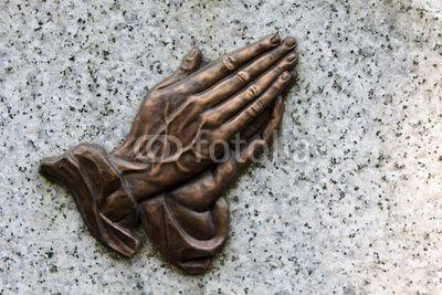 Betende Hände auf einem Grabstein