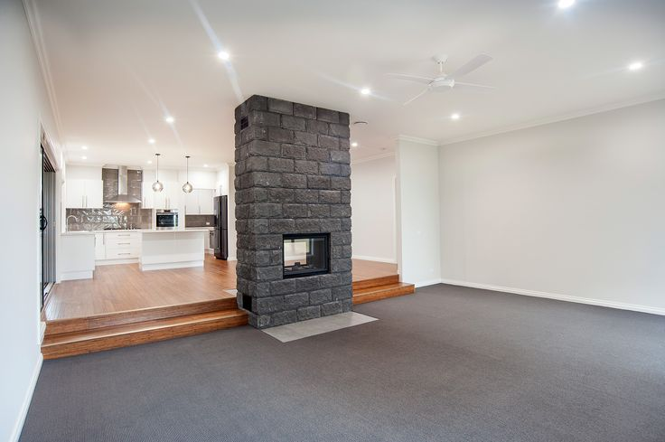Two-sided fire place with concrete block surround. Recessed down-lights. Combination of carpet and bamboo flooring.