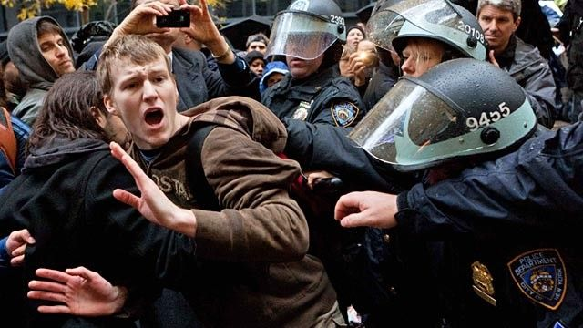 A Occupy Wall Street protester takes it a little too far, as shown by the police grabbing him.