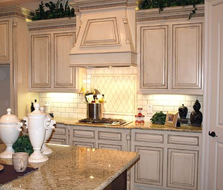 Glazed White Kitchen Cabinets In Combination With Countertops And Backsplashes Of Light Natural