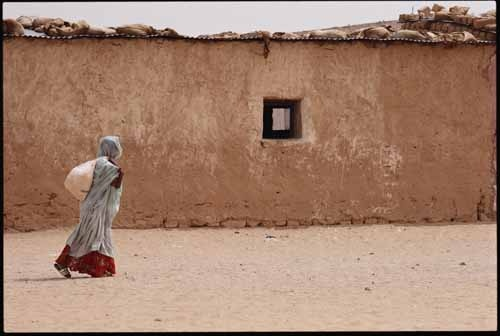 A refugee from Western Sahara leaves a Red Cross food distribution centre with a sack of powdered milk. National Geographic photograph by Steve Raymer, Smara Refugee Camp Near Tindouf, Algeria.