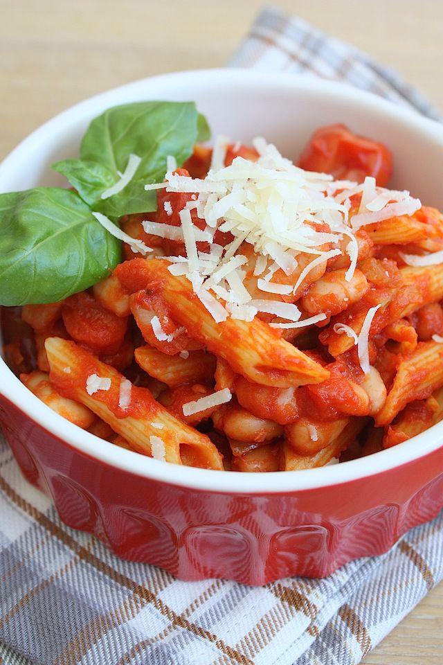 bonen-bolognaise-2 Wat je nodig hebt voor 4 personen  - 500gr penne - zout - 1 ui - 2 teentjes knoflook - 2 wortelen - 1 stengel bleekselderij - 2 potten bonenmix (bijvoorbeeld de kidney-, reuze- en bruine bonen van HAK) - olijfolie - 700ml passata di pomodoro - 1 blik pomodorini of gepelde tomaten - 1 takje rozemarijn - peper - om te serveren: geraspte Parmezaanse kaas en verse basilicum
