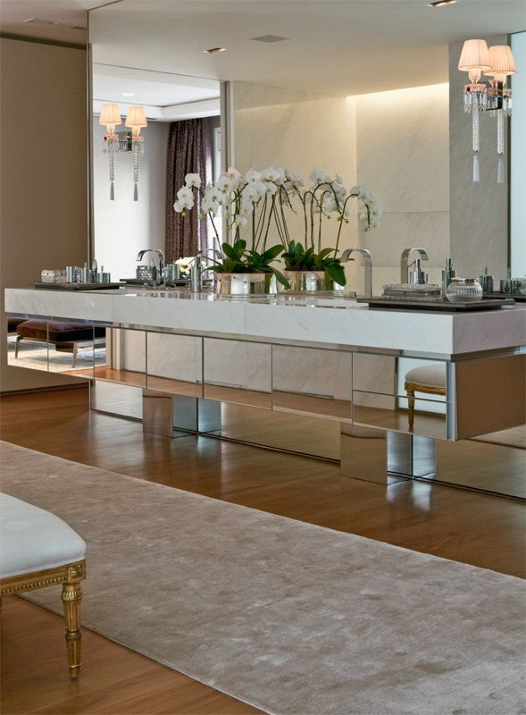 Glam kitchen. Marble and mirrored surface in the kitchen, orchids in silver containers