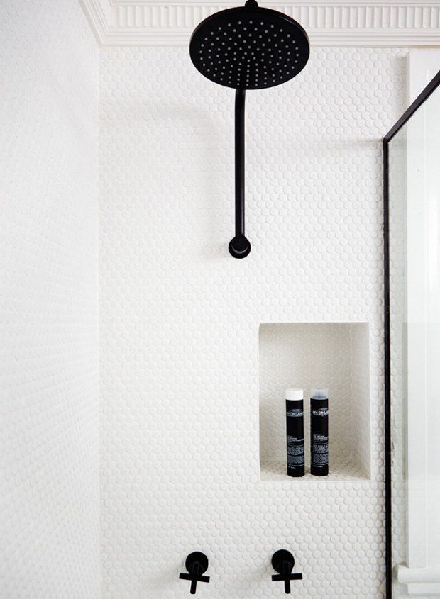 White penny-round tile with white grout lets the matte black hardware stand out in this modern bathroom.