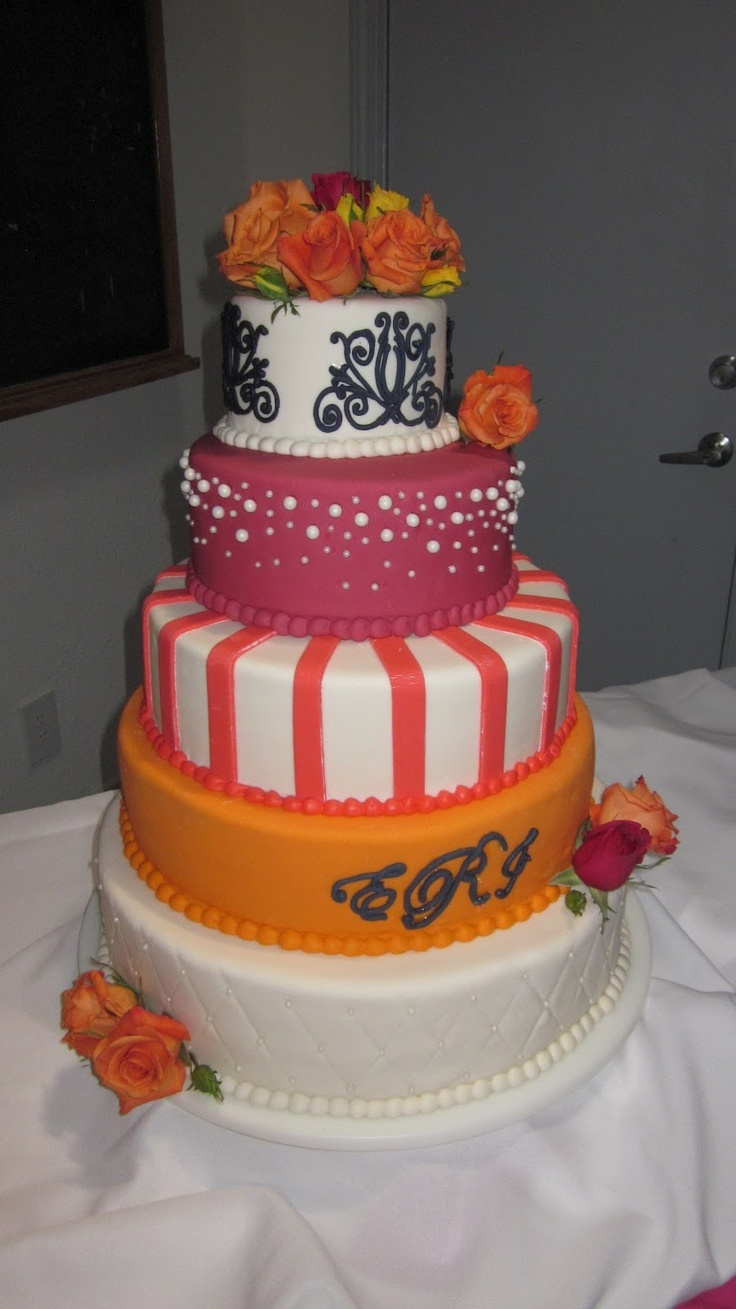 5-tier wedding cake in orange, watermelon, guave, and navy.