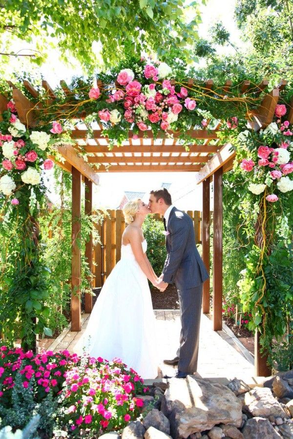Pink wedding arbor. With the flowers distributed in this way it still has a fullness but it would also probably be possible to use floral foam to help keep the flowers fresh.