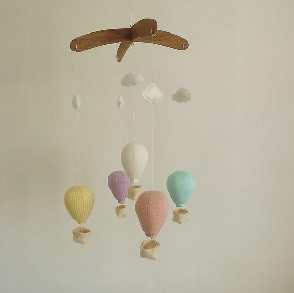 Móbile infantil para pendurar no teto  Estrutura em madeira.  5 Balões em tecido tricoline 100% algodão estampado.  Nuvens em feltro branco  Acompanha um cordão de cetim para pendurar  Tamanho aproximado de cada balão: 15cm com o cestinho.    *Favor consultar estampas disponíveis e prazo de produ...