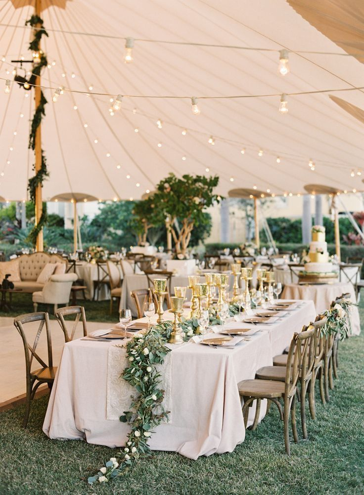 greenery on head table and around poles of tent