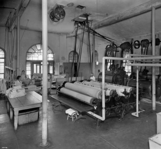 Laundry facility at Agnes Memorial Sanatorium :: Western History | Men and women workers stand in the laundry room at Agnes (Phipps) Memorial Sanatorium in Denver, Colorado. Two women stand at ironing boards and iron hospital gowns. A woman with a bobbed haircut stands near a large folding table where sheets are stacked. A man leans on the large rollers of a pressing machine. Industrial washing machines are against the wall. Date[between 1920 and 1930?]