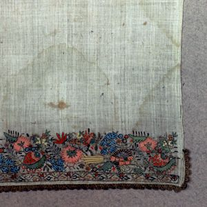 Towel with a four and a half inch embroidered border at each end. The borders, which are identical, have a non-repeating design of flowers and leaves in shades of red, green, blue and metallic silver. The lower border, about an inch high, has a repeating design of curving vines. Each end of the towel is trimmed with gold metallic bobbin lace is sewn across the bottom and four inches up each side.