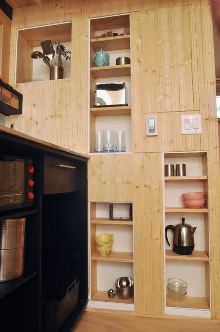 The kitchen features a low-flow faucet and plenty of worktop space, and also includes fridge, freezer, microwave, and a hidden pantry wall