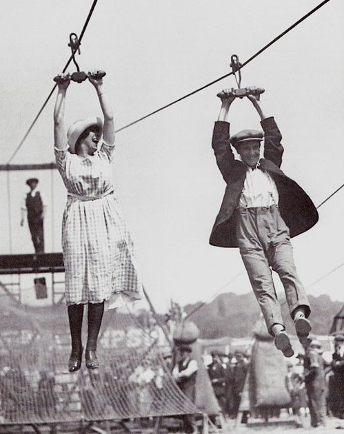 A couple enjoys a zip-line ride, 1920's