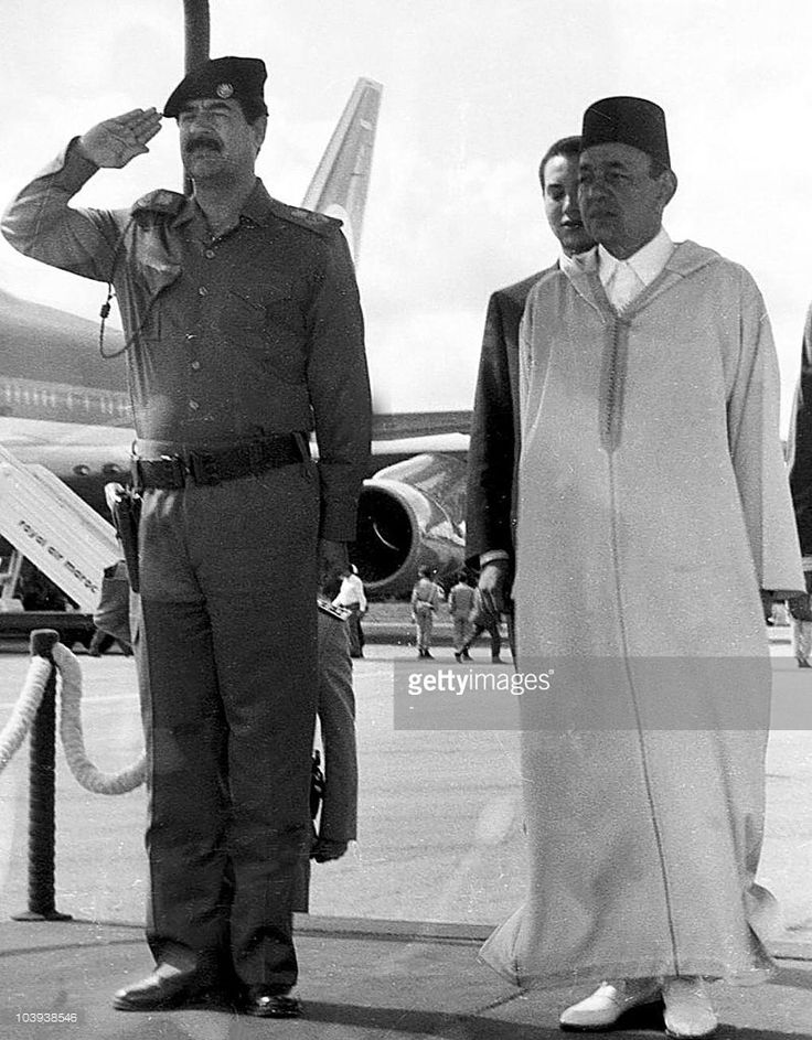 King Hassan II of Morocco (R) and Iraqi President Saddam Hussein stand at attention upon the Iraqi leader's arrival in Rabat for an Arab summit in November 1989. King Hassan II died suddenly 23 July 1999 at the age of 70 after a reign of 38 years. BLACK