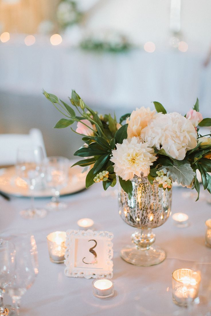 This is what having a mercury glass vase would look like for your flower centerpieces, but your would be sitting on a wood box adding elevation. We then would scatter votive candles around it as shown. What do you think?  Read More: http://www.stylemepretty.com/canada-weddings/2015/05/07/elegant-edwardian-farm-house-wedding-in-vancouver/