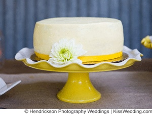 a cheap but sweet single layer white wedding cake on a yellow and white cake stand. (Hendrickson Photography Weddings)