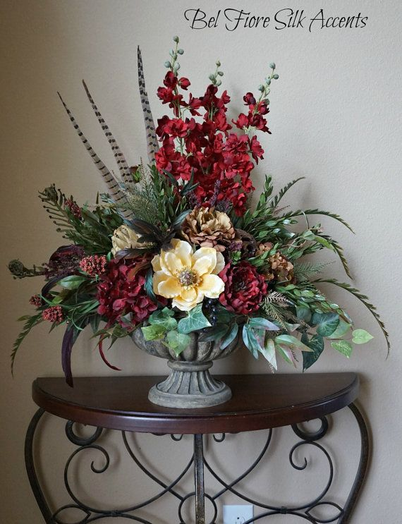Large Tuscan Red Cream and Brown Centerpiece floral Dining Table Arrangement  This Large centerpiece will go beautifully on a breakfast table, entry table or formal dinner table! This resin Tuscan style urn holds red and tuscan brown hydrangea, peonies and delphinium, cream magnolia, dried artichoke, pheasant feathers, coque feathers, and a variety of stunning greenery.  This is an all around arrangement but mainly a front viewed design withe the feathers facing front.  This centerpiece…