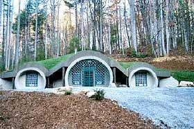 The Hobbit home in Tennessee is more                        of an earth-bermed dome home than it is underground as the                        face of the domes are not compacted with earth (pictured                        left).