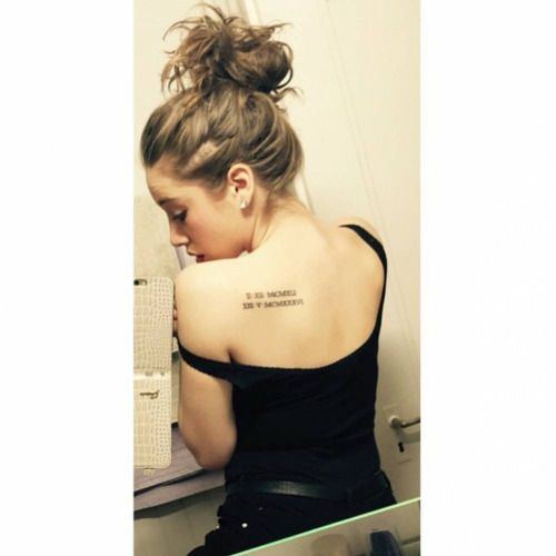 Shoulder blade tattoo of two dates in roman numerals on Tamara.