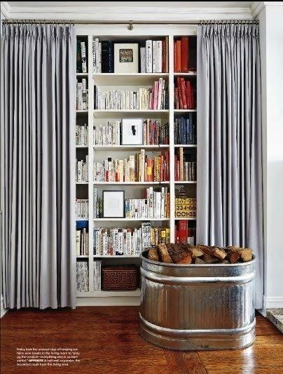 Yes! I will be using this to hide all of the books in our house! Sorry Donny. Brilliant way to visually declutter your space.   Decorator's Trick: Curtains On Bookshelves | Apartment Therapy