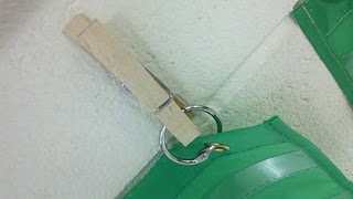 need to get a hot glue gun ASAP!  hot glue, clothespin, notebook ring...hang things on a concrete wall