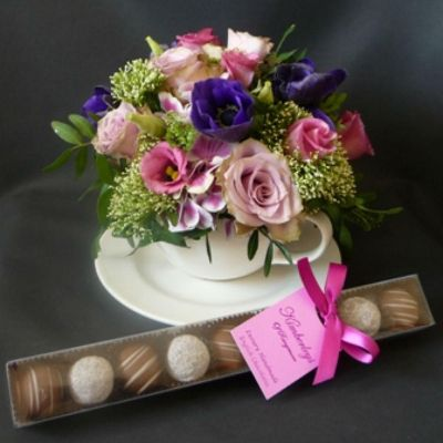 An arrangement of flowers in a teacup, with a free box of chocolates.  Part of our Mothers Day 2016 Collection.