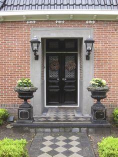 voordeur landelijke stijl mooi met de twee potten op consoles