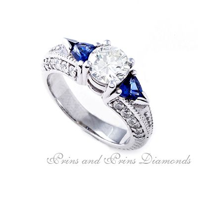 Centre diamond is a 0.96ct M/SI1 round brilliant cut diamond with 25 round brilliant cut diamonds set in the sides of the band and 2 = 0.50ct trillion cut blue sapphires set in a trilogy and side stone 18k white gold design