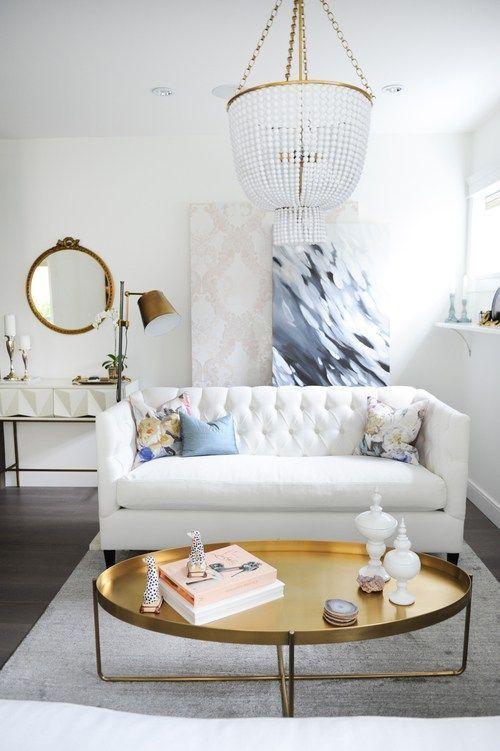 This living space is small but stylish comfortable thanks to its white tufted sofa, gold, oval coffee table, and layered artwork.