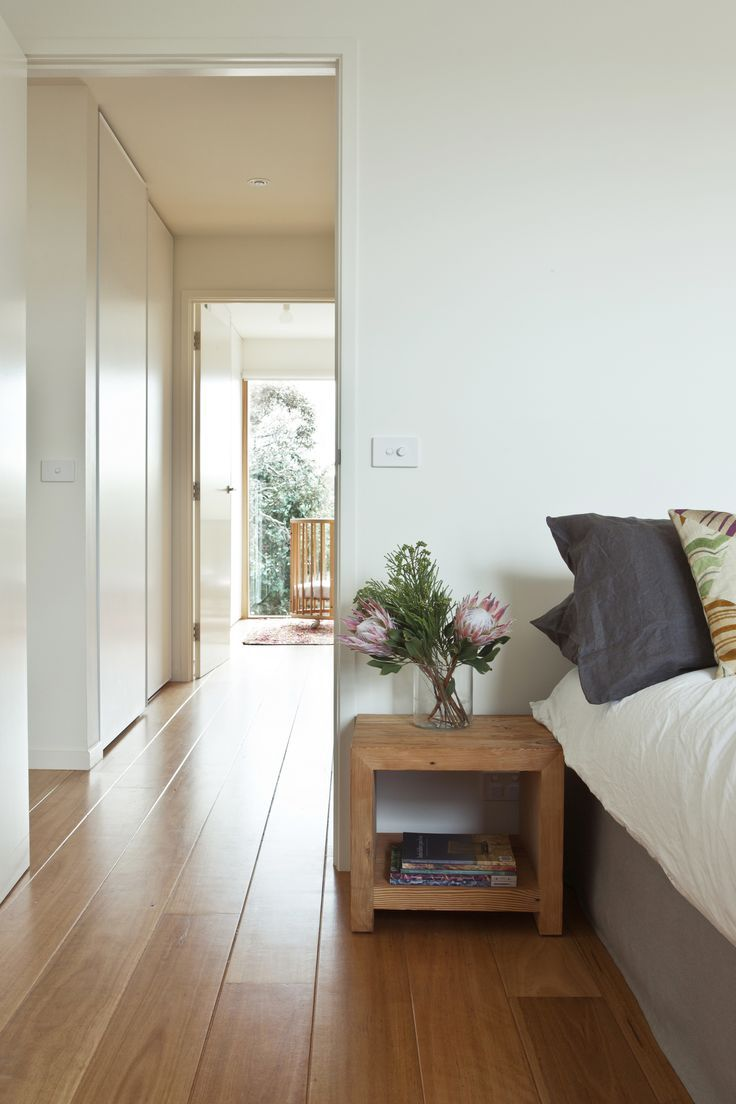 Neutral bedroom with side table and unique floral arrangement on it
