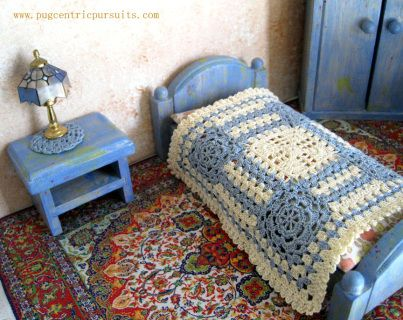 This miniature dollhouse bedspread features an original design.  I crocheted 9 motifs in very fine blue and ecru cotton thread.  5 inches square.  Pugcentric Pursuits.