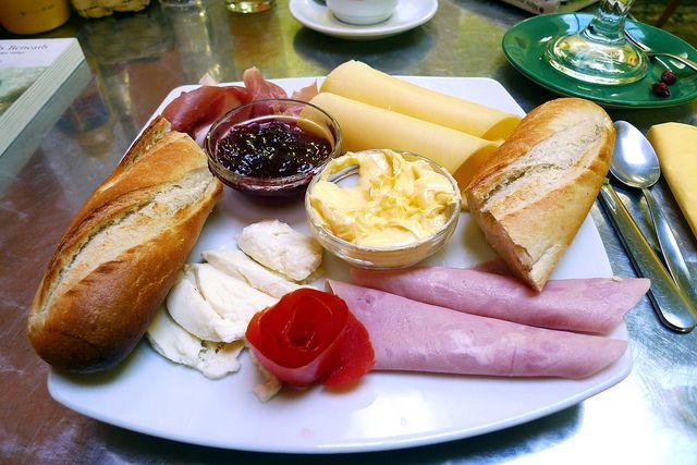 No #Brasil, basicamente, come-se o quanto pode: queijos, frios, geleias, sucos, frutas e, claro, pães e bolos de todos os tipos. Fora o café bem forte. Ou seja, uma mesa de café-da-manhã bem servida e o seu estômago estará garantido por boa parte do dia.