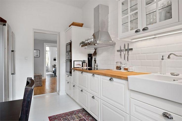 Drewniany blat w przyjemny sposób urozmaica aranżację białej kuchni. Jasna podłoga dodatkowo rozświetla pomieszczenie i...