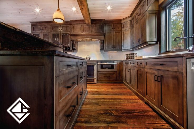 In this rustic beauty, man has made the most of what nature offers. The hand-hewn beams and scraped floors frame the room with a masterful blend of grains, patterns and hues that could only be found in the great outdoors. With a natural weathered finish, the cabinets add texture along with many storage options.