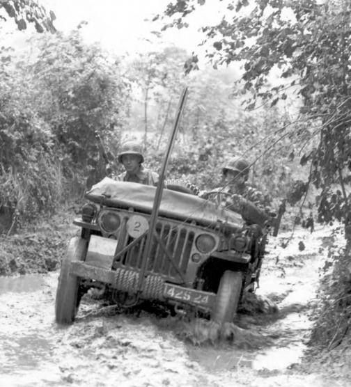 Jeep travels through flooded roads in Normandy, France, circa July 1944. On the front of the jeep is an iron bar used to cut thin strands of wire that the enemy strung across the roads level with the heads of the occupants of open vehicles.