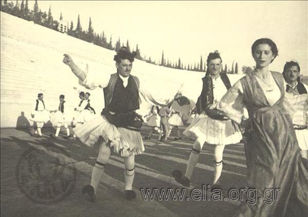 Εορτασμοί της 4ης Αυγούστου: γυναίκες και άνδρες χορεύουν με παραδοσιακή ενδυμασία από την Στερεά Ελλάδα 1937. Nelly's (Σεραϊδάρη Έλλη)
