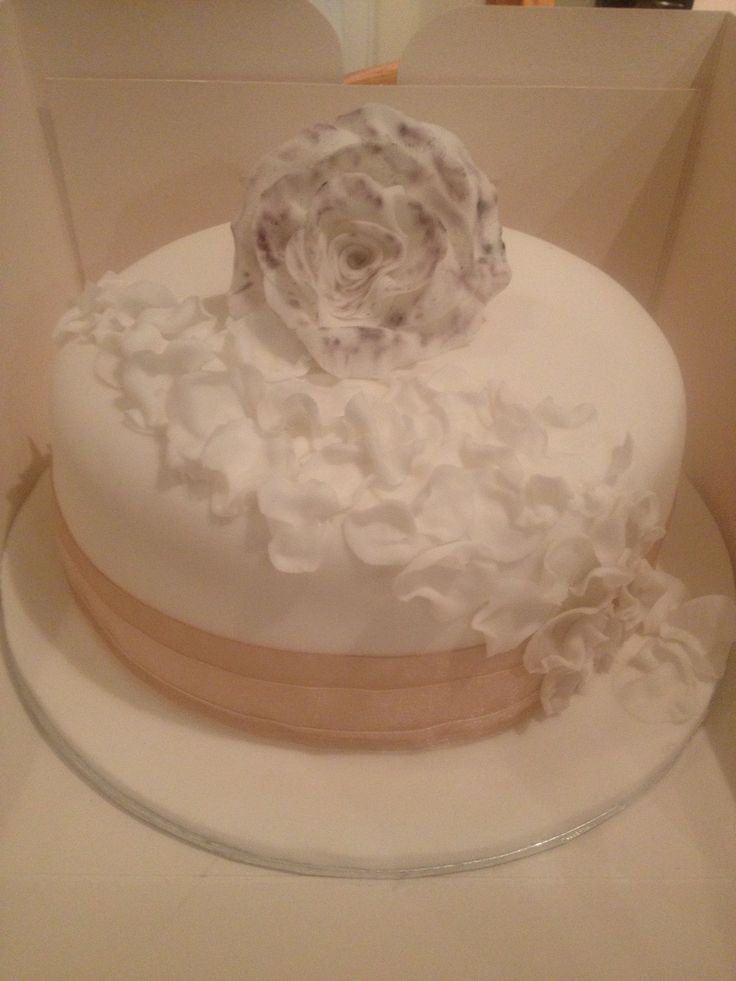 Pretty celebration cake with handmade rose and petals