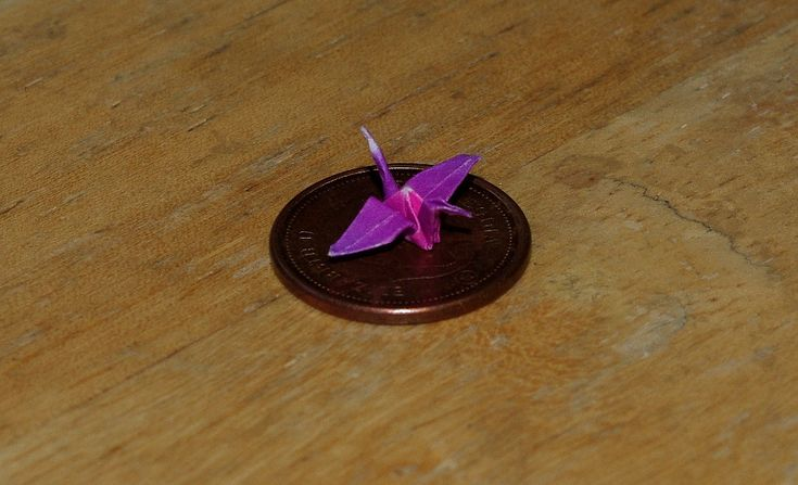 Origami crane Smaller then a penny by Melanie Cormier. Origami earrings and other jewelry here: https://www.facebook.com/trendcreations?ref=bookmarks