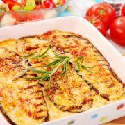 Griekse Moussaka   ngrediënten  150 gram geraspte oude brokkelkaas (overjarig)3 kleine of 2 grote aubergines nootmuskaat1 grote ui 2 tenen knoflook1,5 deciliter olijfolie 500 gram gehakt1 blikje tomatenpuree 1 eetlepel paprikapoeder1,5 theelepel kaneel 5 literblik gepelde tomaten op sap4 takjes peterselie 1,5 deciliter witte wijn40 gram boter 40 gram bloem4 deciliter melk 2 eieren