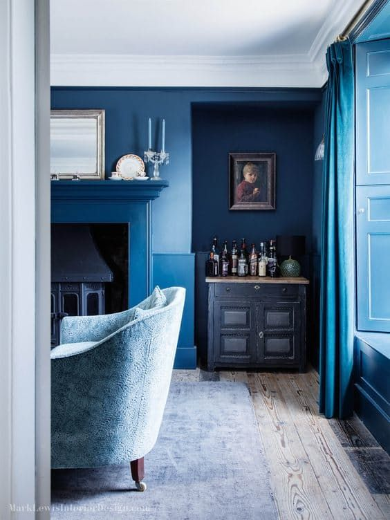 This rich blue of the walls and drapes in this room by Mark Lewis Interior Design almost glows.