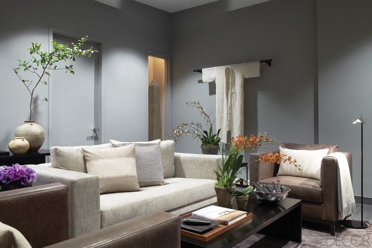 """As you enter the home's lower level, a calm, serene library provides an urban retreat for the homeowners. """"It's their private place to recharge, and the palette reflects this,"""" says Amy Mellen, creative director of Calvin Klein Home. The designer concentrated on subtle nuances in color and texture for the room, hallmarks of the line. """"I focus on mixing materials when I design, so it was interesting to see how the fabrics worked with the antiques that we incorporated, like the beautiful…"""