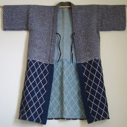 Sashiko stitched, indigo dyed cotton coat, mid-20th century. Stitched decoration is in equal proportion on top & bottom: the top half is a densely stitched field of small, cross shapes, while the bottom is a more open, lattice pattern.