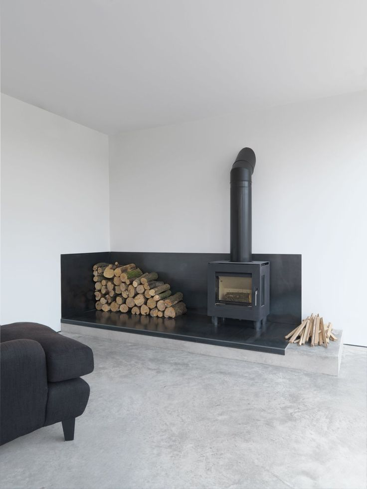 Black, minimal focal point in this 1970s build, extended fireplace with log storage and wood burner | Feversham House by McLaren Excell