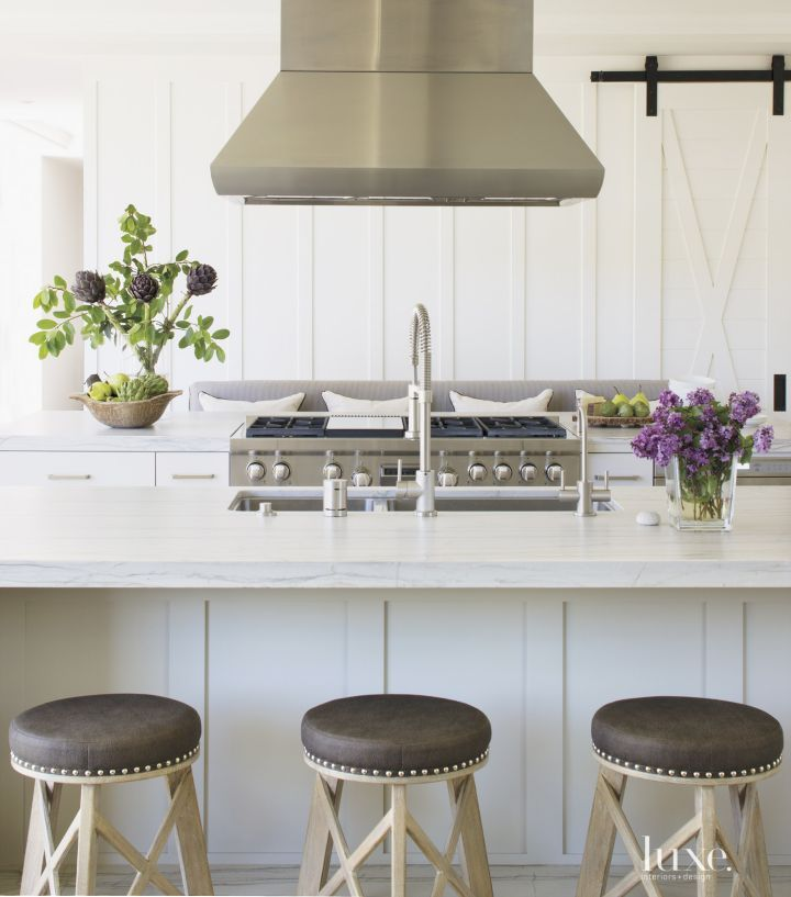McCormick chose Madigan side chairs by Hickory Chair and slipcovered Restoration Hardware host chairs to encircle a sturdy Restoration Hardware table in the dining area. Overhead is a custom iron fixture by Gibson & Gibson Antique Lighting.