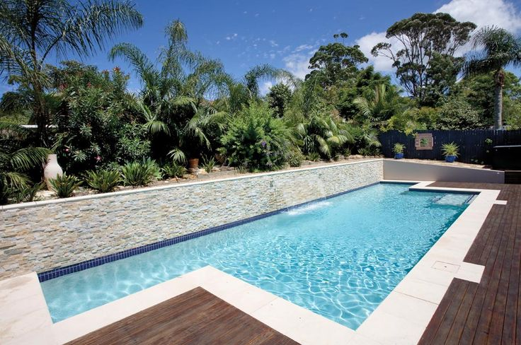 This in-ground lap pool features an up-stand-wall finished with a Stack Stone, a sheer descent waterfall, hardwood decking along with glass pool fencing