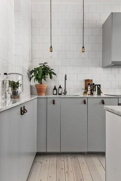Grey modern and minimalist kitchen cabinets with a touch of blue in the paint, dark leather DIY drawer and cabinet pulls, glossy white square tile backsplash done in alternating brick pattern, industrial black and brass single bulb pendant lights, and potted plants and indoor terrariums on the gray and white carrara marble kitchen counter tops.