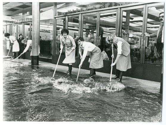 Haringey, Marks & Spencer's workers clear flood water in Wood Green, 1981
