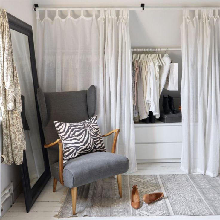 Garderober. Sovrummet har snedtak och för att få så bra förvaring som möjligt har paret byggt klädförvaring, med skira, vita gardiner som hänger framför kläderna. Fåtöljen är köpt i en antikaffär och omklädd. Kudden har Ulrika sytt. Matta från House doctor. Spegel och gardiner från Ikea.