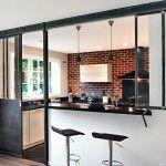 Lumineuse et conviviale, cette cuisine s'ouvre sur le séjour grâce à une verrière en acier de style industriel, en grande partie coulissante.
