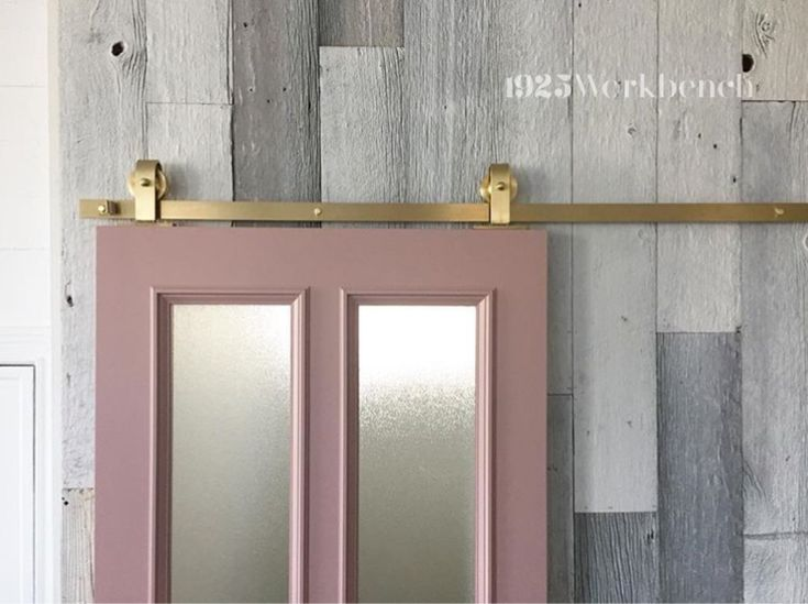 Our  Brassy Beau top mount barn door hardware, made of solid brass on our handmad pink door. Made in Canada  #brasshardware #barndoorhardware #pinkdoor
