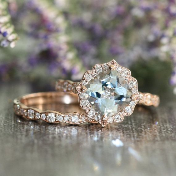 This bridal wedding ring set showcases a vintage inspired floral engagement ring with a 8x8mm cushion cut natural aquamarine crafted in a solid 14k